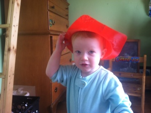 Sassy miss toddler, trying out a new approach to wearing her brother's fire hat.