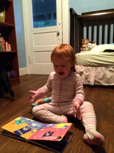 Reading her current favourite book to herself on the floor of her new room.