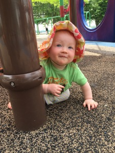 A little flower in the center of her sun-hat, Tathy peeks around a playground post to say hello.
