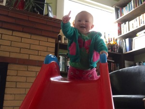 Victorious, and proud every time of the victory, Tabitha climbs the slide ladder and confidently waves her arms around (this is a pointing exercise.  You're supposed to meet her finger with your own, Michelangelo).